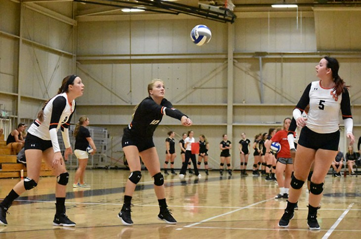 Nicole Reichert digs as a ball as Erika Halverson (left) and Ashley Pickert look on.